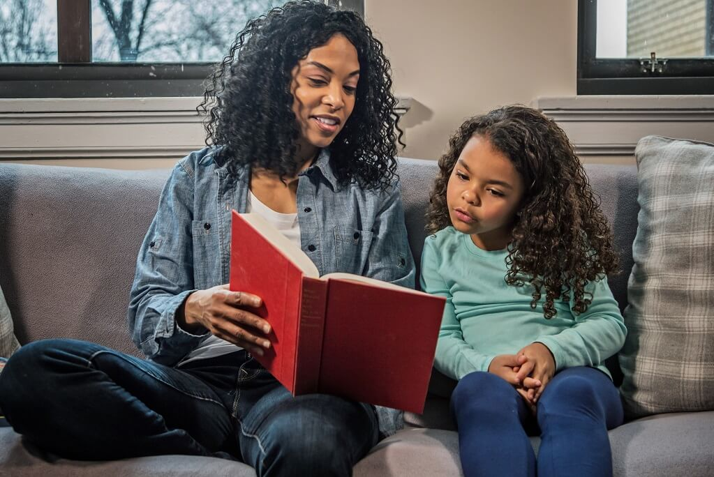mom reads book to daughter while sitting on couch