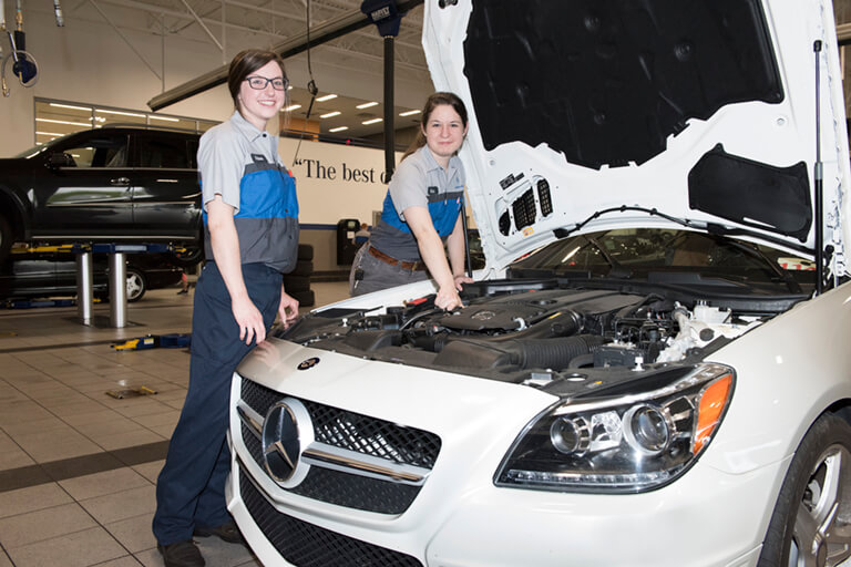 two female students working underneath the hood of a white car. text overlay reads Auto Tech