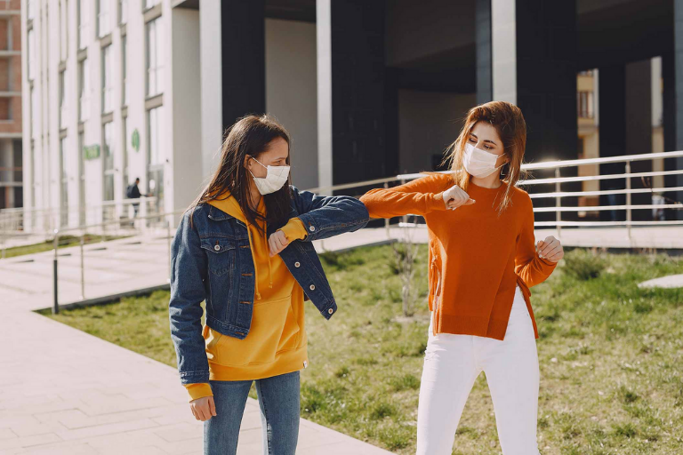 two girls bumping elbows wearing face masks
