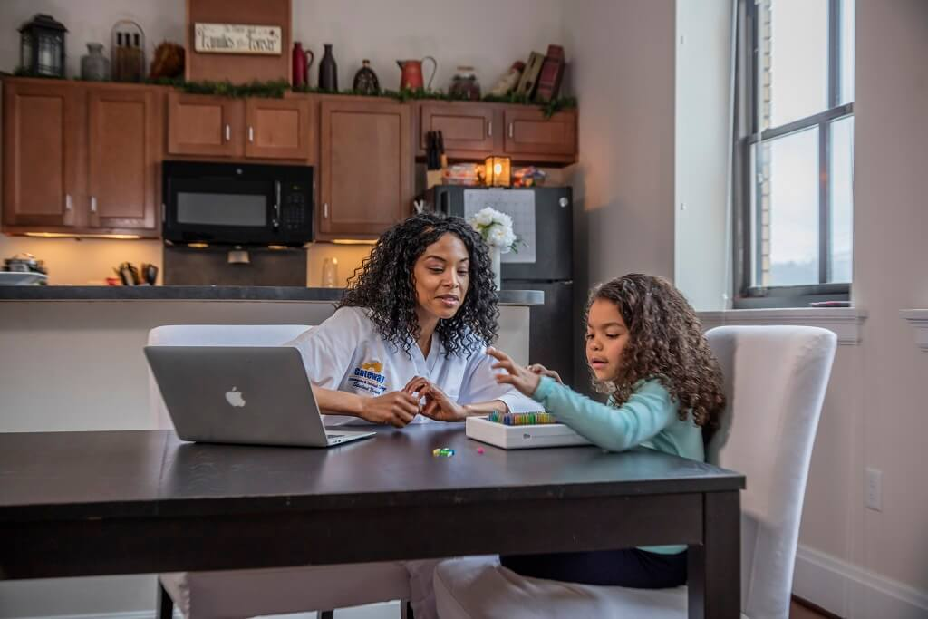 mom working on computer in kitchen while daughter plays at table
