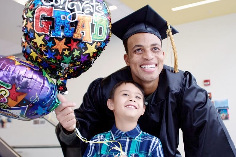 Man in cap and gown posing with child and holding balloons