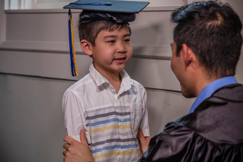 dad puts graduation cap on son